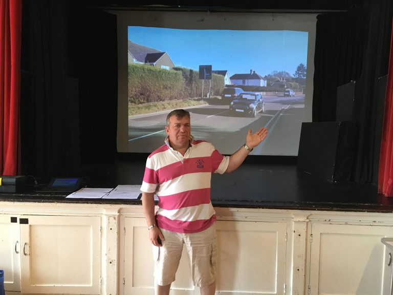 photograph of Steve Wright presenting in front of a projected image of traffic on the A21