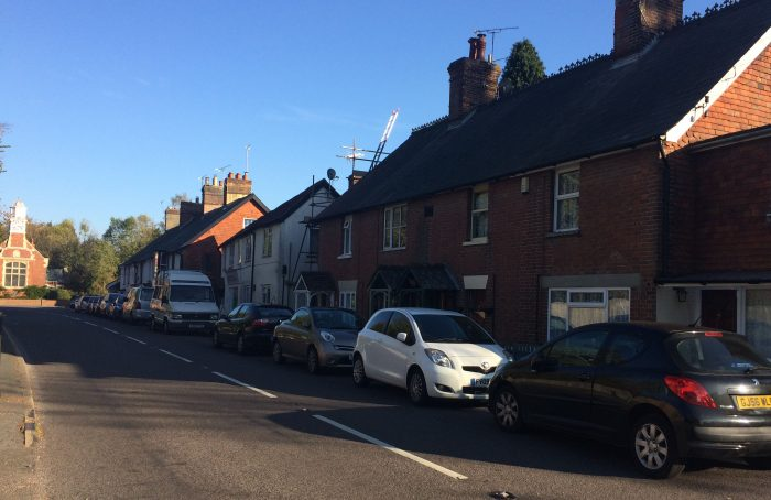 photograph of houses and cars on station road